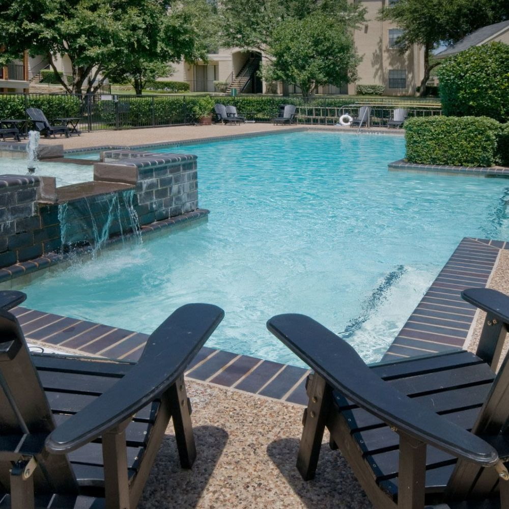 Fountain and chaise lounge chairs near the resort-style pool at Rockbrook Creek in Lewisville, Texas