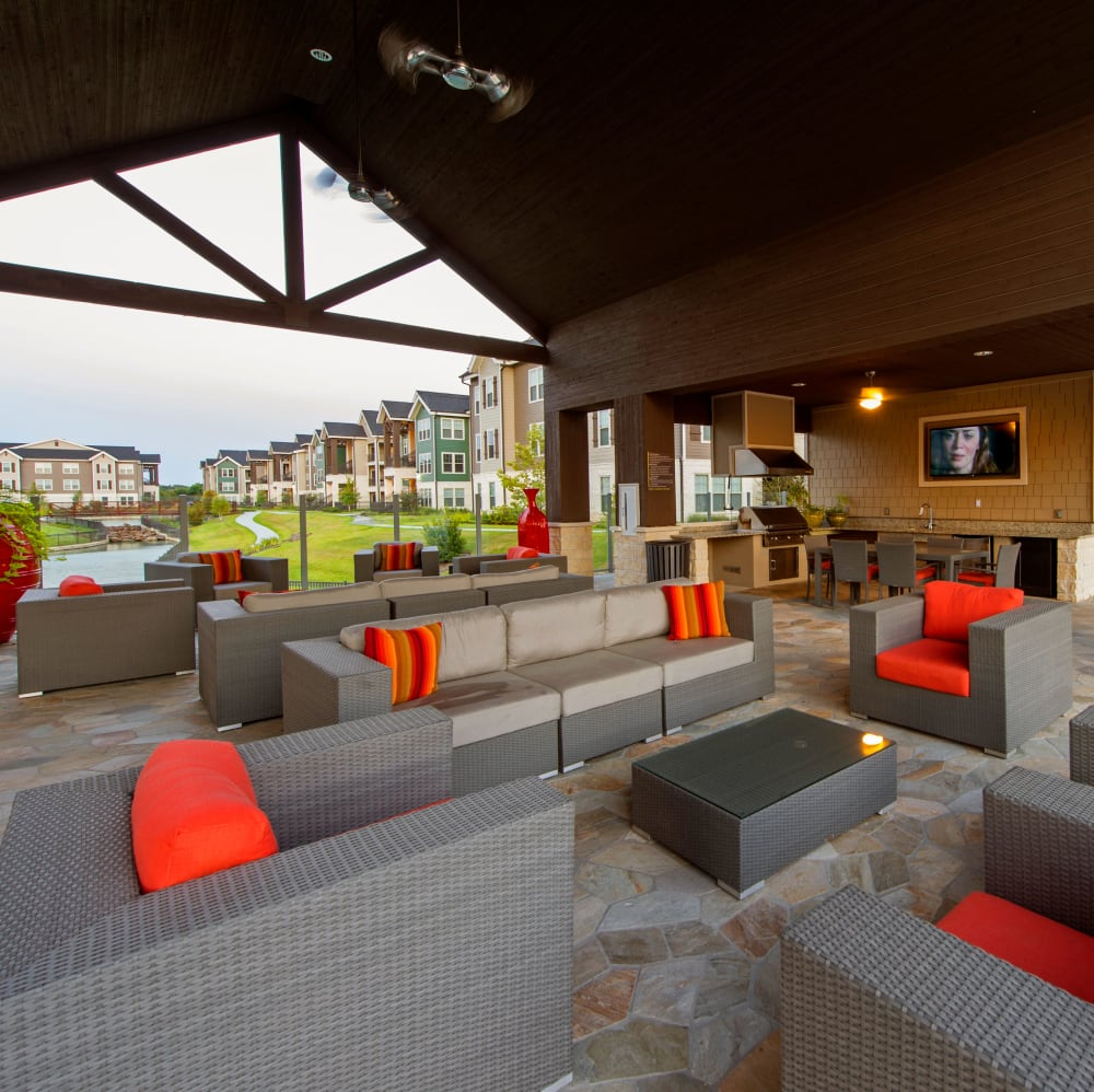 Covered outdoor lounge with TVs at Elite 99 West in Katy, Texas