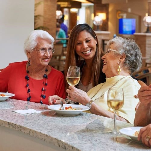 Residents enjoying appetizers and wine in the bistro at Celebration Village Acworth in Acworth, Georgia