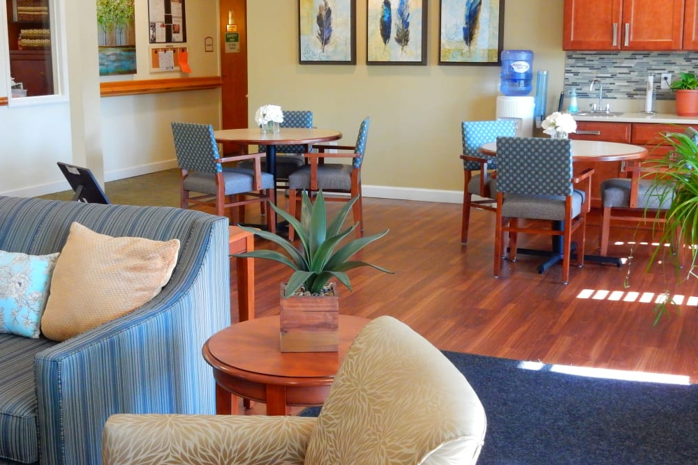 Charming sitting area with tables at upscale senior living facility with armchairs and wood accentsat Carriage Court of Grove City in Grove City, Ohio