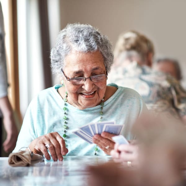 A resident playing a card game at The Crest at Citrus Heights in Citrus Heights, California.