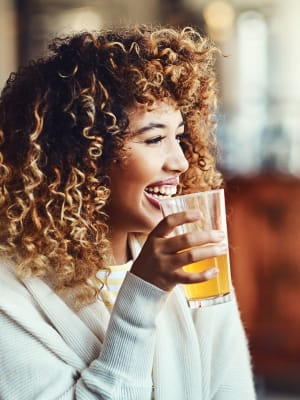 A woman enjoying a craft beer at a brewery near M2 Apartments in Denver, Colorado