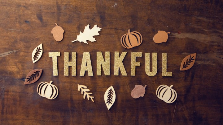 """the word, """"thankful"""" surrounded by seasonal fall decor cut-outs of leaves, and pumpkins."""
