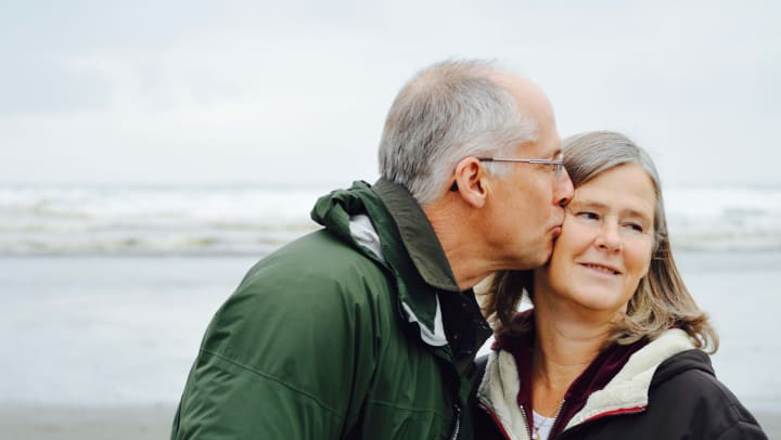 elderly couple on the beach posing for photo