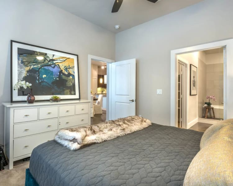 Plush carpeting and a ceiling fan in a model home's bedroom at Macallan at Ross in Dallas, Texas