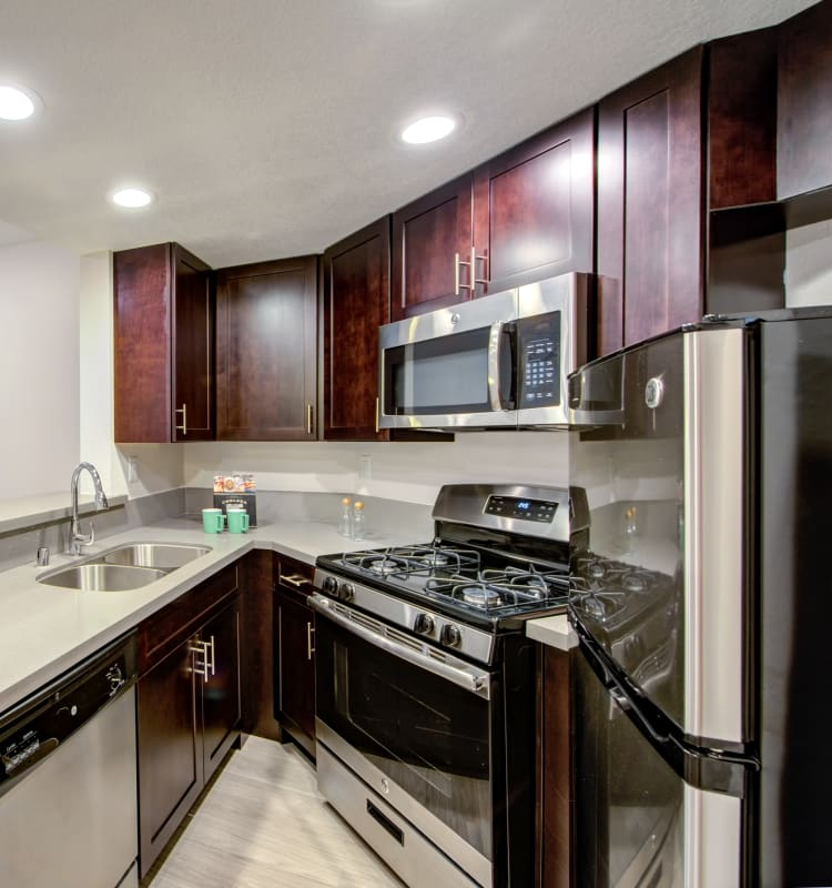Modern kitchen with sleek, stainless-steel appliances and a gas range in a model home at Sofi at 3rd in Long Beach, California
