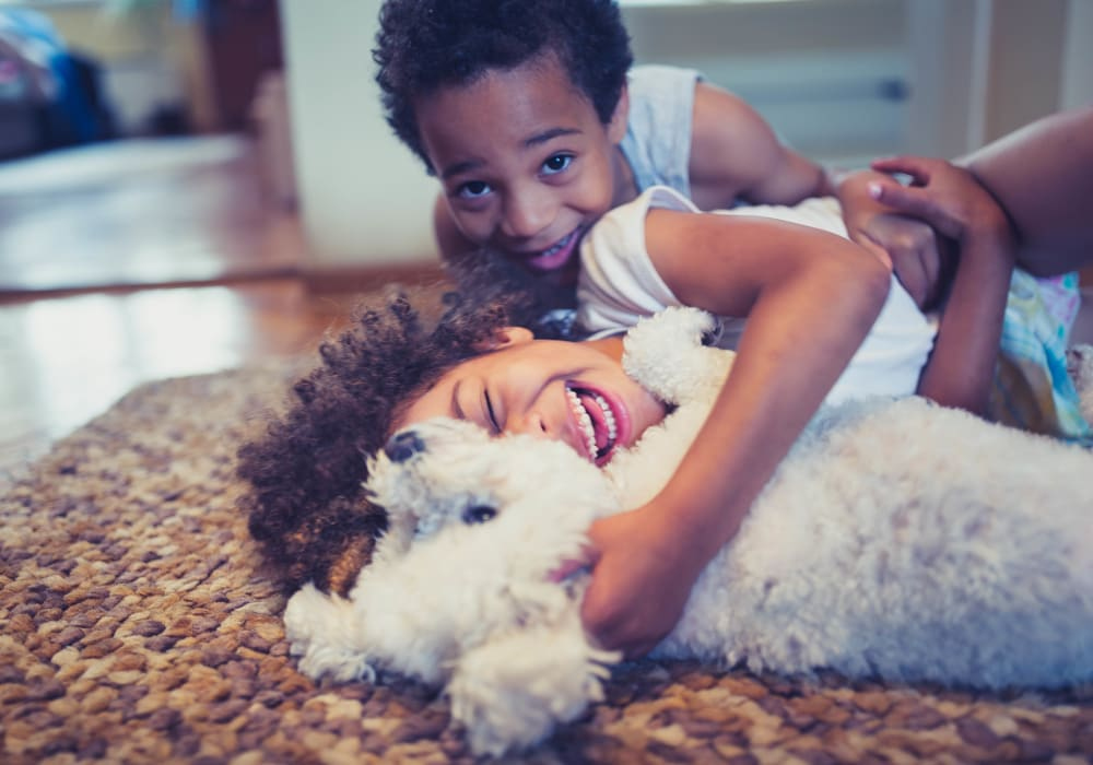 Resident children and their puppy loving their new home at another community by at Olympus Property in Fort Worth, Texas
