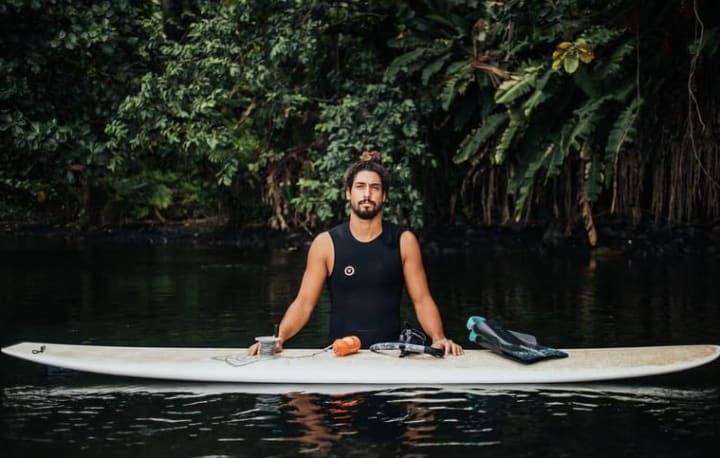 Dr. Cliff Kapono standing in hip-high water, with his hands on a surfboard that's in the foreground