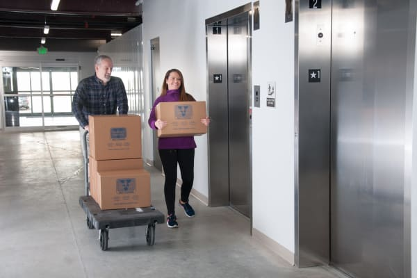 A couple moving boxes on a dolly Virginia Varsity Storage in Roanoke, Virginia