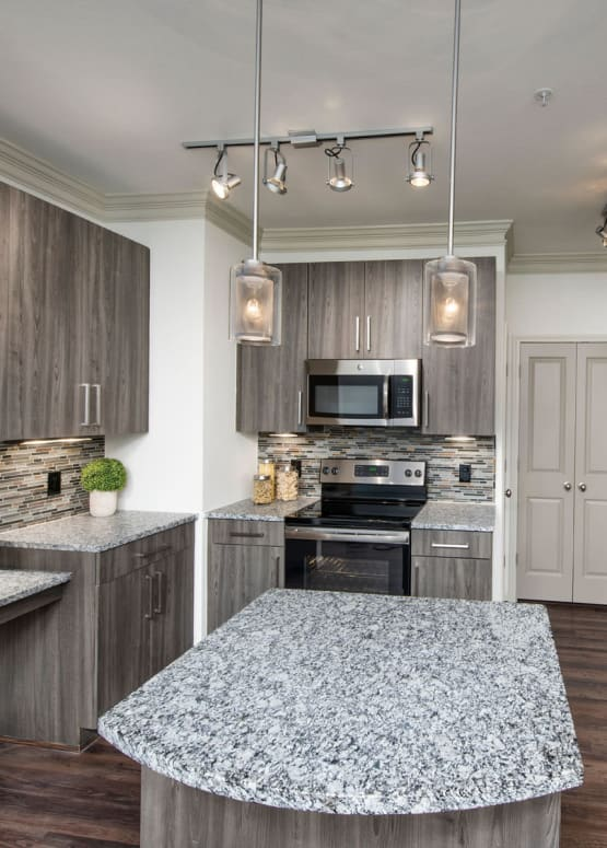 Modern kitchen with stainless-steel appliances and granite countertops in a model apartment at The Heights at Sugarloaf in Duluth, Georgia