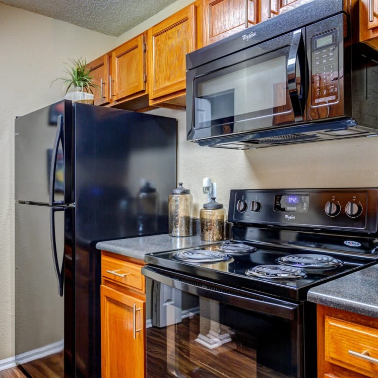 Modern kitchen with granite-style countertops and all-black appliances in model home at Lyric on Bell in Antioch, Tennessee