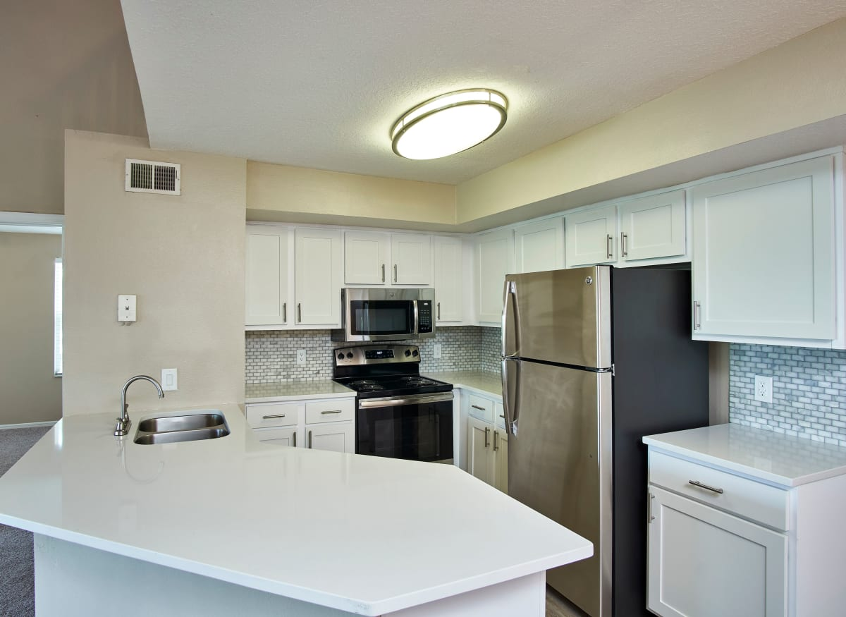 A large kitchen with white cabinets at Calais Park Apartments in St Petersburg, Florida
