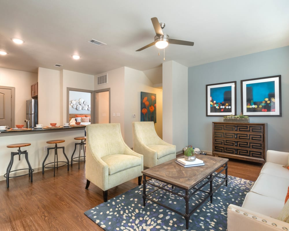 Large open-concept living area with hardwood floors and a ceiling fan in a model home at Olympus Waterford in Keller, Texas