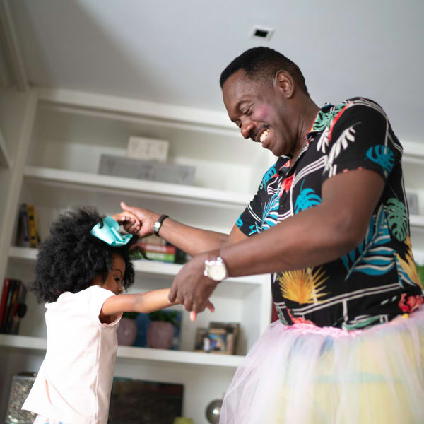 A man and his granddaughter play dress up at Kenmore Senior Living in Kenmore, Washington