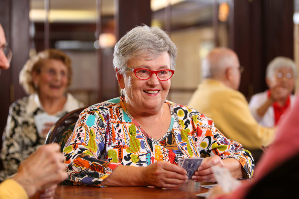 Resident happily playing a card game at Brookstone Estates of Mattoon North in Mattoon, Illinois