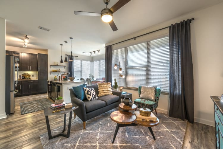 Well-furnished model home's living area with a ceiling fan at Mercantile River District in Fort Worth, Texas