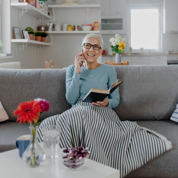 A resident sitting in her cozy apartment at Pacifica Senior Living Fresno in Fresno, California.