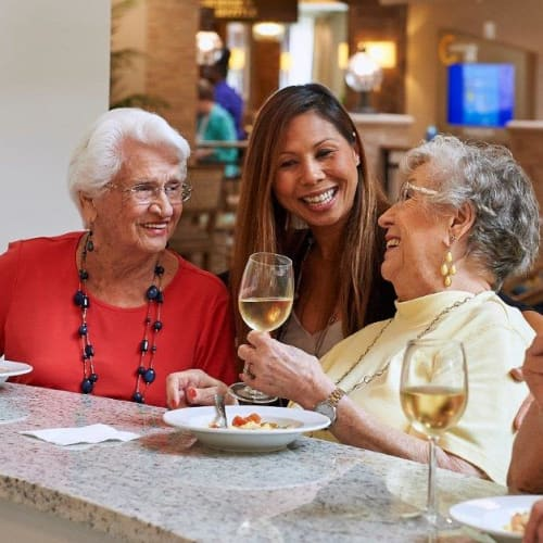 Residents enjoying talking with staff in the bistro at The Crossings at Eastchase in Montgomery, Alabama