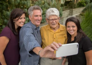 Senior resident and family taking a picture with a phone