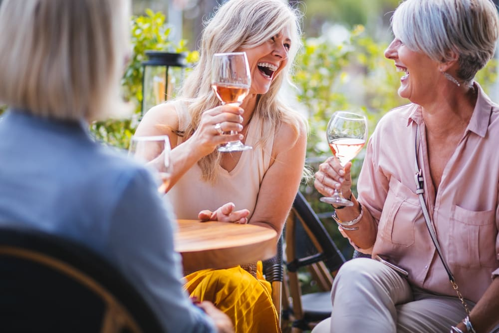 Three ladies enjoying conversation and beverages outside at Elegance Living, LLC in Baltimore, Maryland