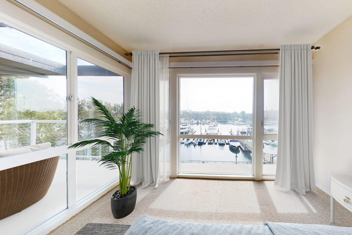 Large windows with views of the marina inside a spacious bedroom at The Tides at Marina Harbor in Marina del Rey, California