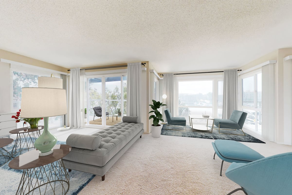 Living room inside an open-concept apartment home with large windows overlooking the marina at The Tides at Marina Harbor in Marina del Rey, California