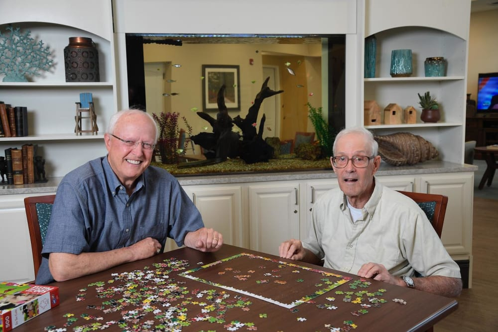 Residents making a puzzle at a CERTUS Premier Memory Care Living community.