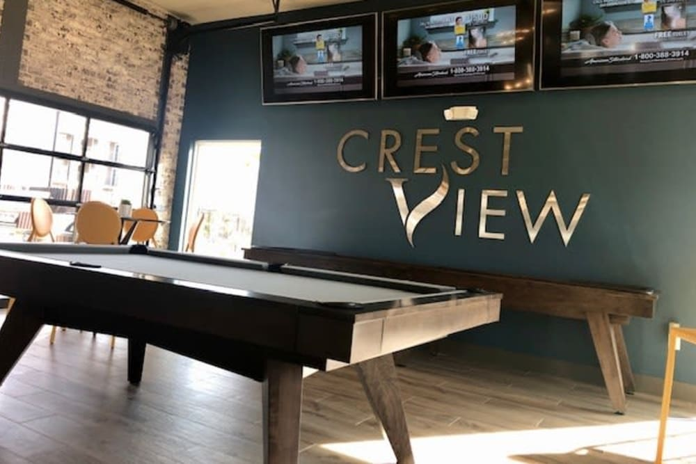 Game area in clubhouse with televisions at Cottages at Crestview in Wichita, Kansas