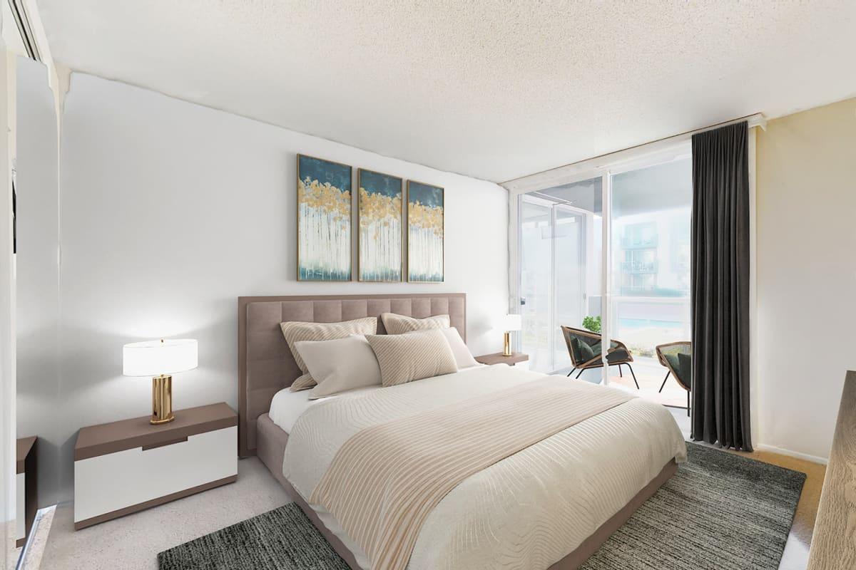 Spacious bedroom with plush carpeting and balcony at Waters Edge at Marina Harbor in Marina Del Rey, California