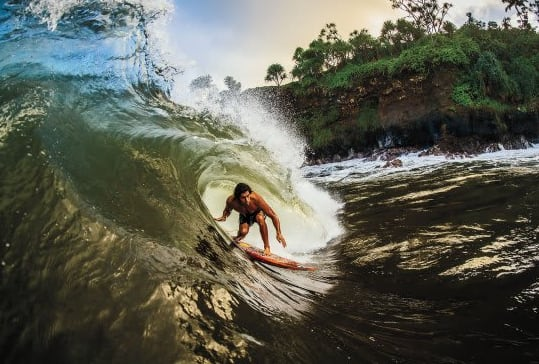 Dr. Cliff Kapono surfing a big wave