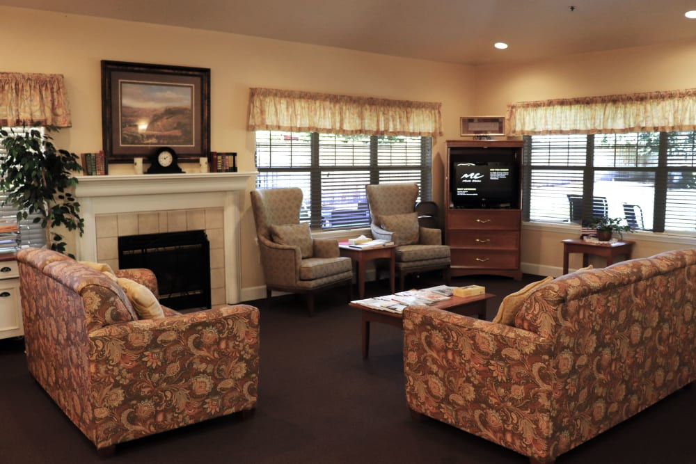 Charming sitting area complete with comfortable sofas, television set, and fireplace in upscale senior living facility at The Springs at Willowcreek in Salem, Oregon