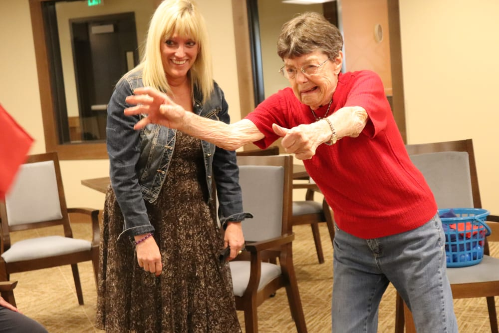Resident and caregiver playing a game at The Springs at Bozeman in Bozeman, Montanag