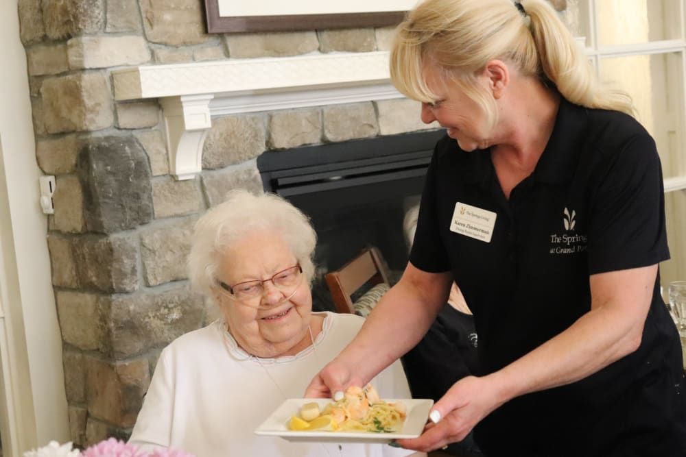 Resident being served a meal by caregiver at The Springs at Grand Park in Billings, Montana