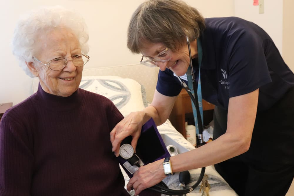 Resident with caregiver taking her blood pressure at The Springs at Butte in Butte, Montana