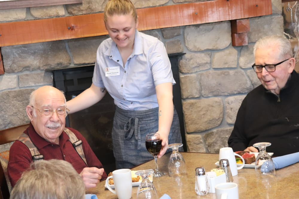 Two residents enjoying a meal with a dedicated caregiver at The Springs at Butte in Butte, Montana