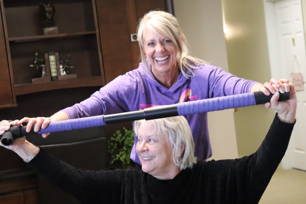 Resident and caregiver having fun participating in an exercise class at The Springs at Butte in Butte, Montana