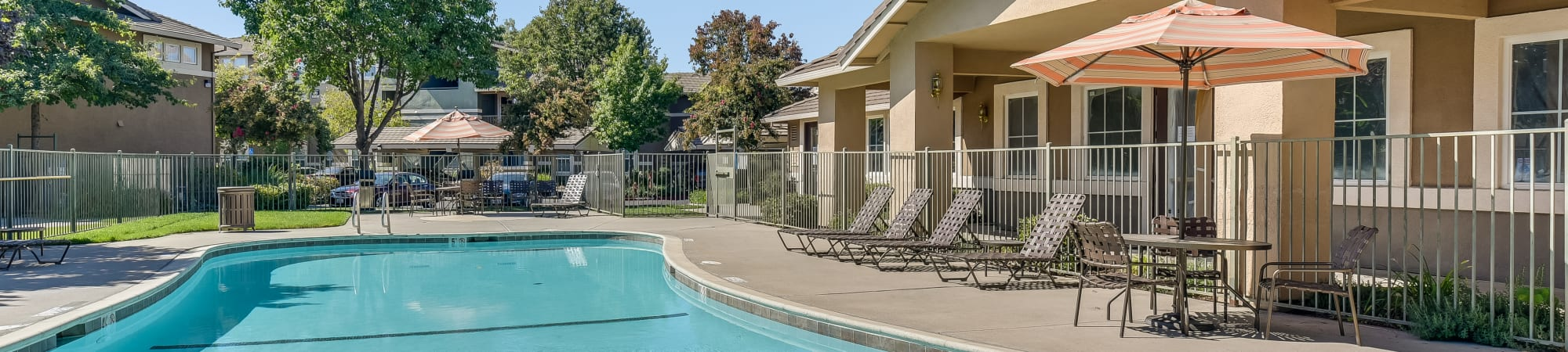 Elegant outdoor area with lawn chairs and pools at Natomas Park Apartments in Sacramento, California