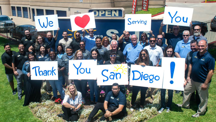 Group of staff members holding up San Diego signs