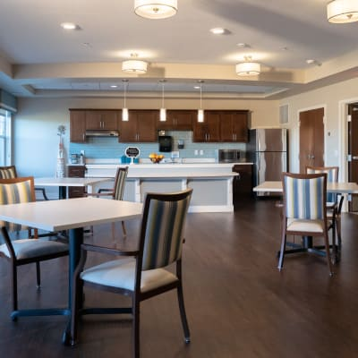 Modern community space with kitchen and tables for gathering at The Sanctuary at St. Cloud in St. Cloud, Minnesota