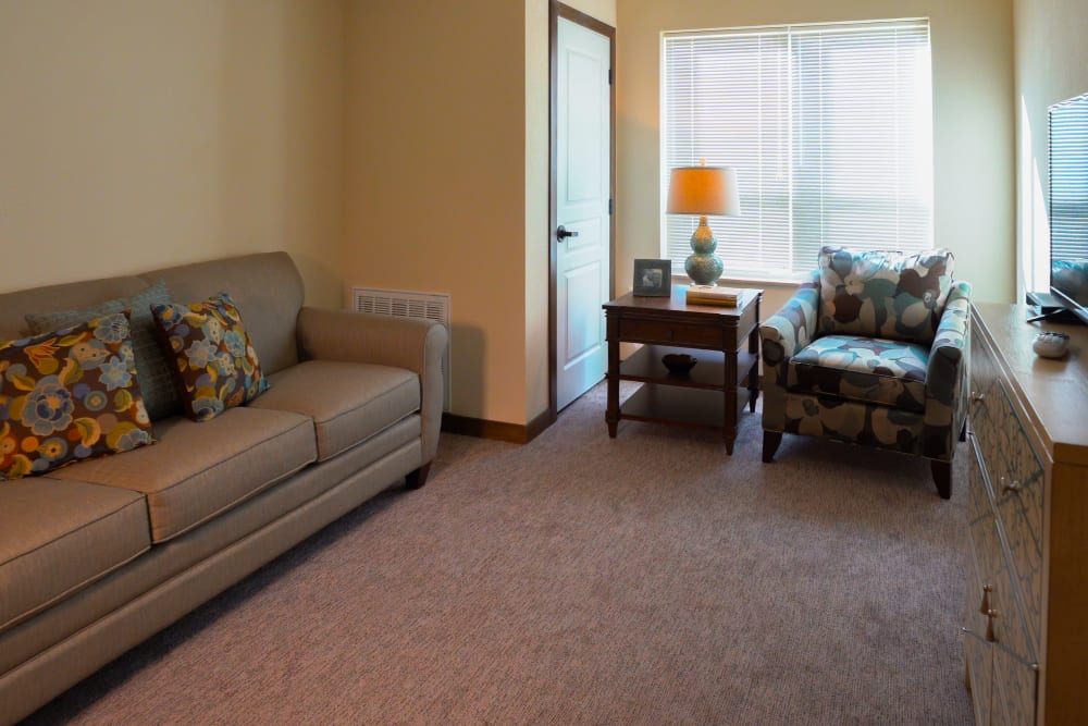 Living room with a couch and a chair at Deephaven Woods in Deephaven, Minnesota
