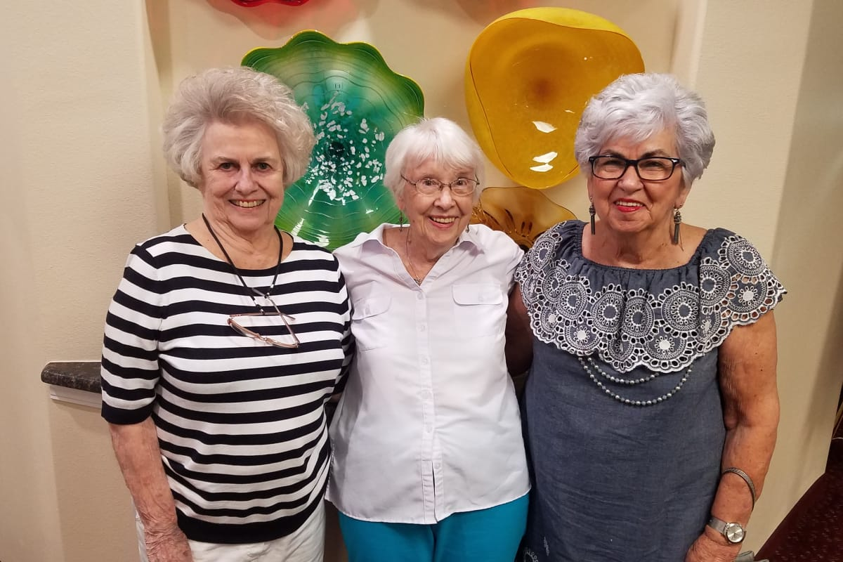 3 Senior women posing for a photo with their arms wrapped around each others shoulders at Hawthorn Senior Living in Vancouver, Washington