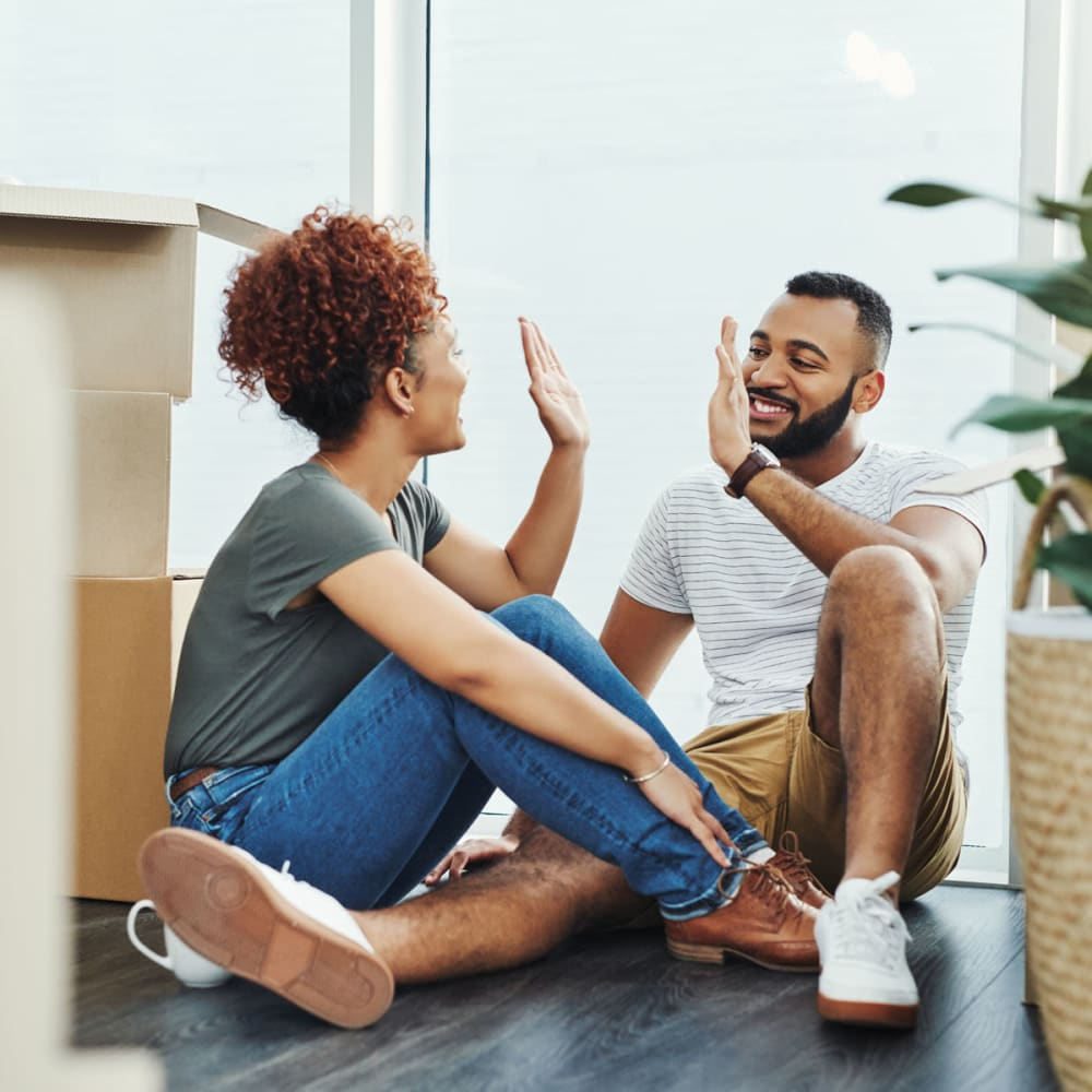 Couple high-fiving after moving all their belongings into their new apartment home at The Retreat at Arden Village Apartments in Columbia, Tennessee