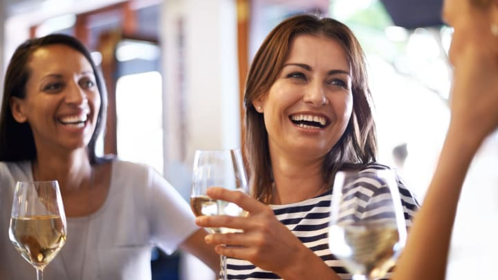 Three women smiling at one another and holding glasses of white wine.
