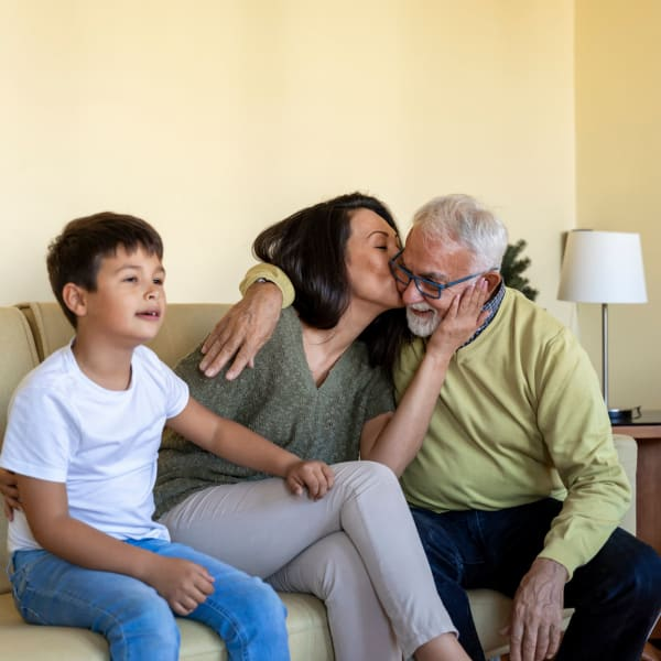 Family embracing in a living room at Pacifica Senior Living Sterling in Sterling, Virginia