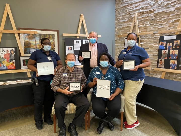Team members at Woodstock (GA) take a photo together in front of the Black History Month display.