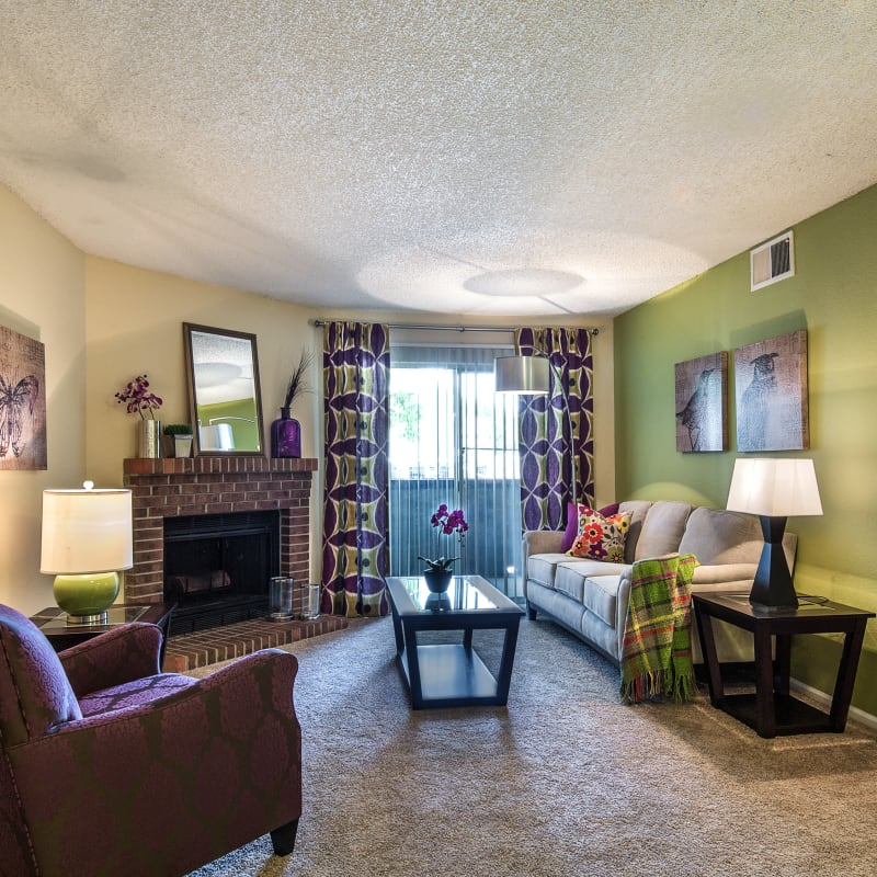 Well-furnished living area with a fireplace in a model home at Waterfield Court Apartment Homes in Aurora, Colorado