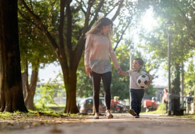 Resident mom walking her son to school near Foundations at River Crest & Lions Head in Sugar Land, Texas
