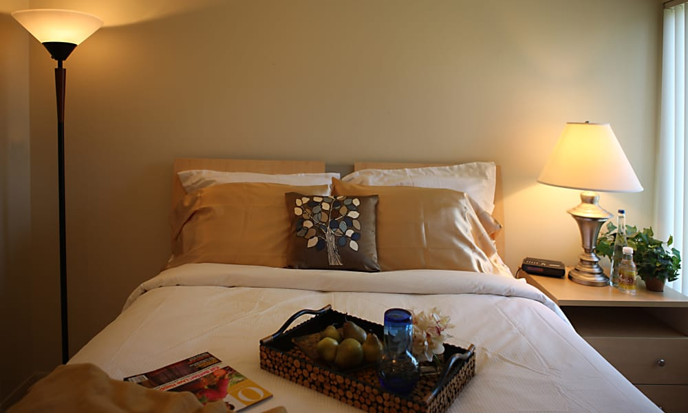 Comfortable bed in model home at Kensington Manor Apartments in Farmington, Michigan