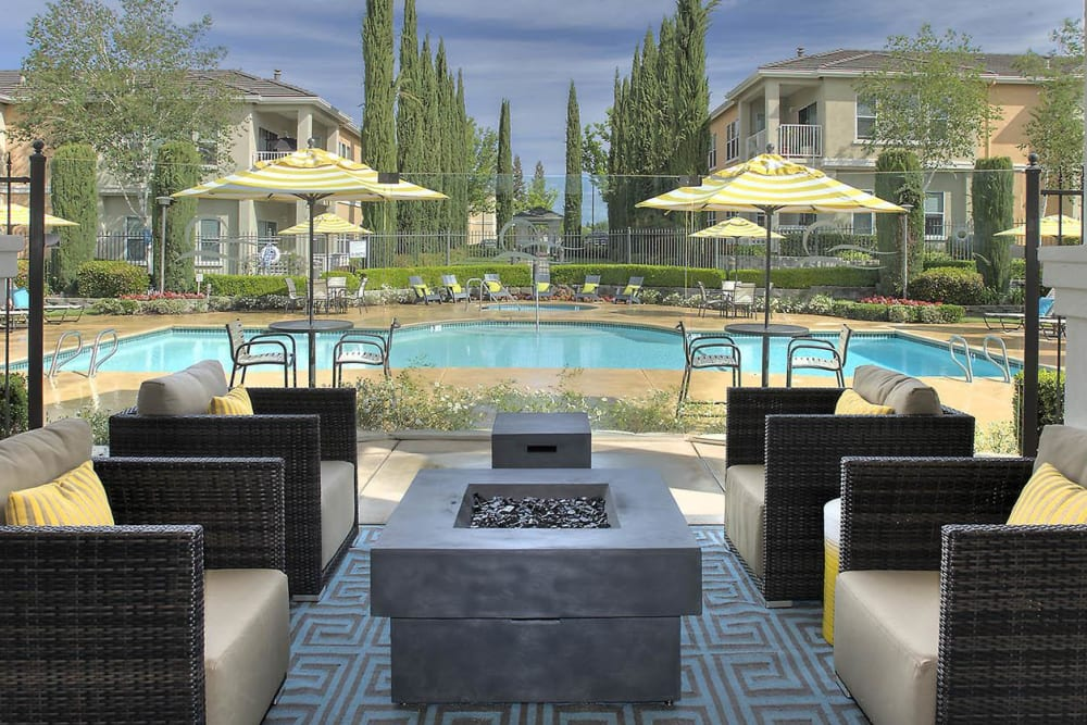 Outdoor cabana with a fireplace and comfortable seating at Iron Point at Prairie Oaks in Folsom, California