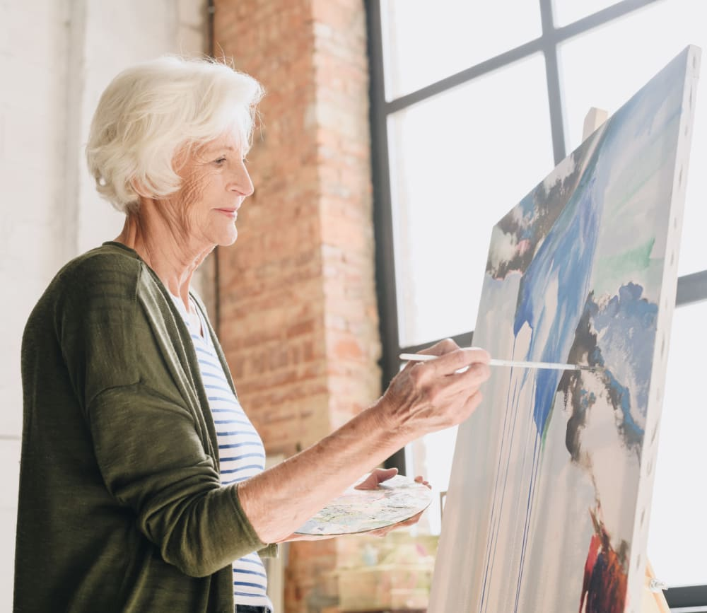 Woman resident painting at Clearwater at North Tustin in Santa Ana, California